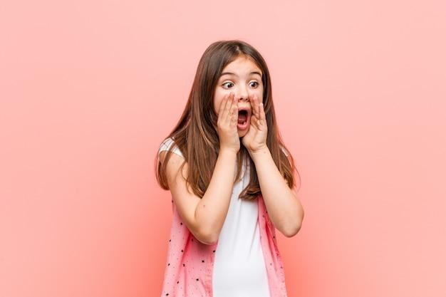Schattig klein meisje schreeuwt luid, houdt ogen open en handen gespannen.
