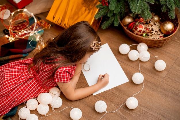 Schattig klein meisje schrijft brief aan de kerstman