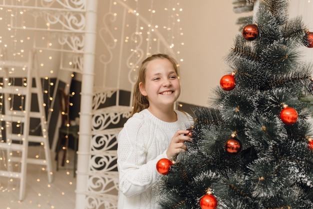 Schattig klein meisje siert de kerstboom met nieuwjaar speelgoed en rode ballen. een meisje in een witte gebreide trui en jurk staat hangende ballen op een kunstmatige spar