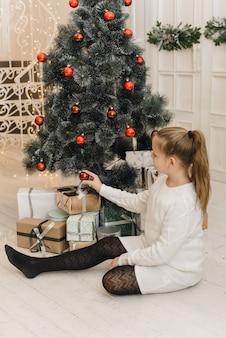 Schattig klein meisje siert de kerstboom met nieuwjaar speelgoed en rode ballen. een meisje in een witte gebreide trui en jurk zit naast geschenken en hangt ballen aan een kunstmatige spar
