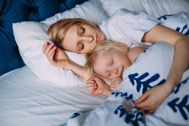Schattig klein meisje slapen met moeder in bed. interieur. conceptzorg
