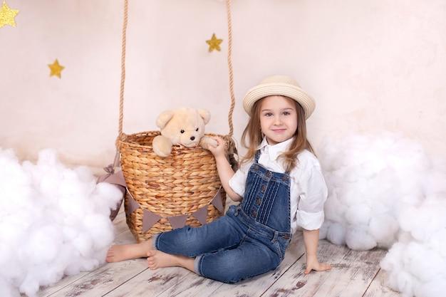 Schattig klein meisje speelt in een kinderkamer met een teddybeer en een ballon.
