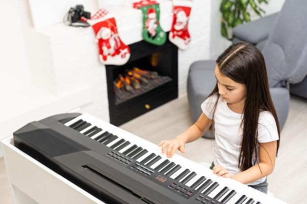 Schattig klein meisje speelt kerstmelodie op piano, vrolijk kerstfeest, fijne seizoensvakanties