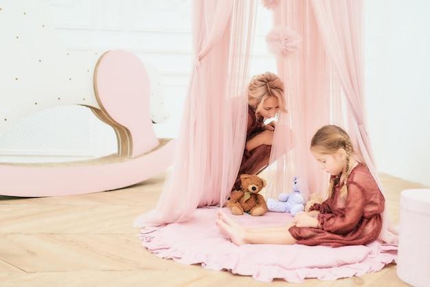 Schattig klein meisje speelt met een beer in speelgoed huis