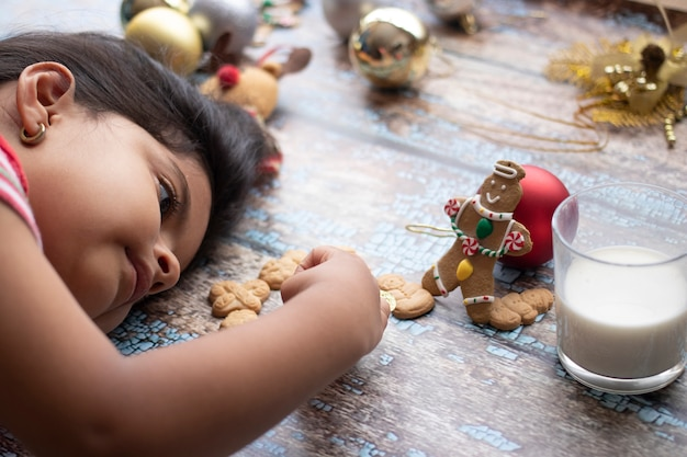 Schattig klein meisje speelt met kerstkoekjes en melk met kerstmis