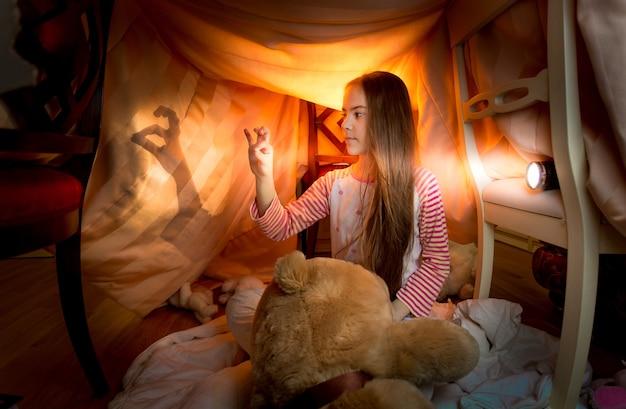 Schattig klein meisje speelt 's nachts in het schaduwtheater in de slaapkamer