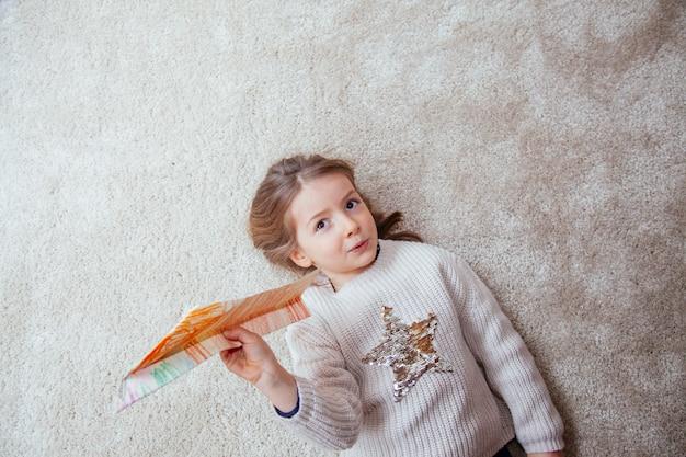 Schattig klein meisje spelen met een papieren vliegtuigje