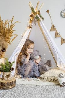 Schattig klein meisje spelen met een teddybeer in een wigwam thuis. nieuwjaars versieringen.