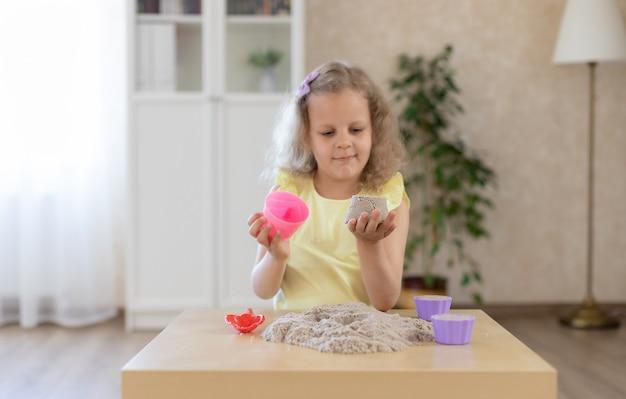 Schattig klein meisje spelen met kinetisch zand