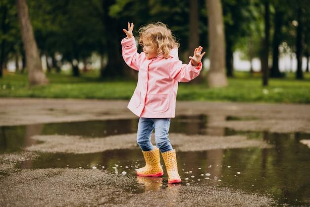 Schattig klein meisje springen in plas in een regenachtig weer