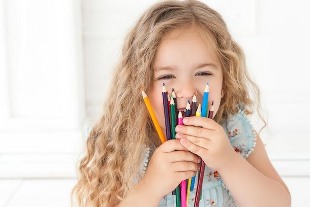 Schattig klein meisje tekenen met kleurrijke potloden op papier. mooi klein kind tekenen binnenshuis. schattige kunstenaar. mooi meisje dat haar gezicht met potloden ineenkrimpt en bij camera glimlacht.