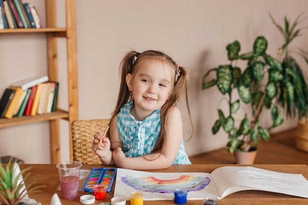 Schattig klein meisje tekent met een penseel en verf aan de tafel in de woonkamer