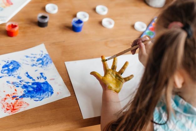 Schattig klein meisje tekent met verf en handen geschilderde handpalmen voor kinderen