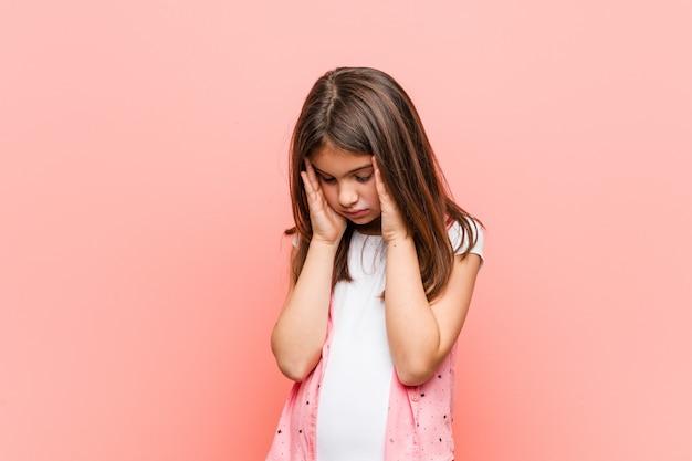 Schattig klein meisje tempels aan te raken en hoofdpijn te hebben