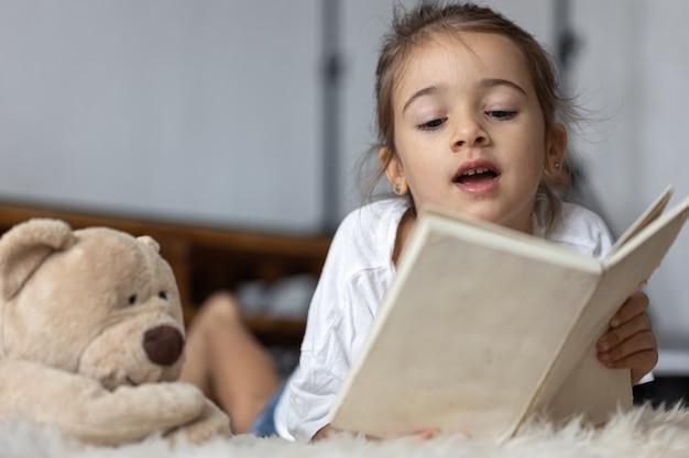 Schattig klein meisje thuis, liggend op de vloer met haar favoriete speeltje en leest boek.