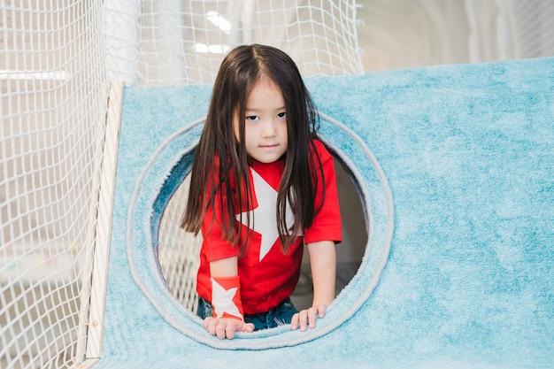 Schattig klein meisje van aziatische afkomst in kostuum van super meisje op zoek naar jou tijdens het spelen in zacht huis op speelplaats