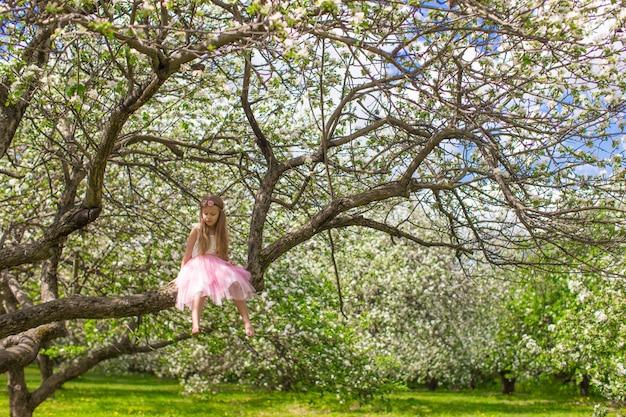 Schattig klein meisje veel plezier in bloeiende appelboomgaard