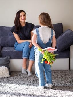 Schattig klein meisje verrassende moeder met bloemen