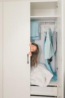 Schattig klein meisje verstopt in de kledingkast