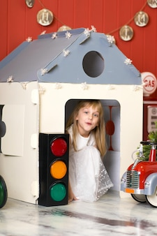 Schattig klein meisje verstopt in een kartonnen huis en spelen met een grote stuk speelgoed brandweerwagen