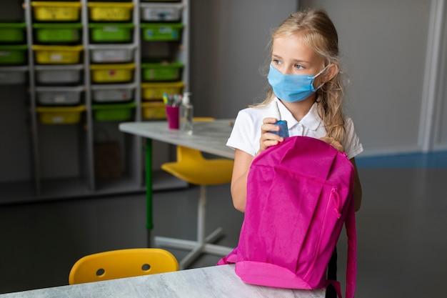 Schattig klein meisje wegkijken terwijl het dragen van een medisch masker