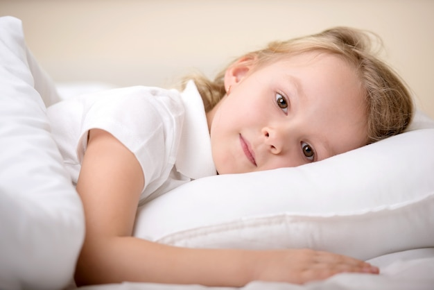 Schattig klein meisje werd wakker in haar bed.