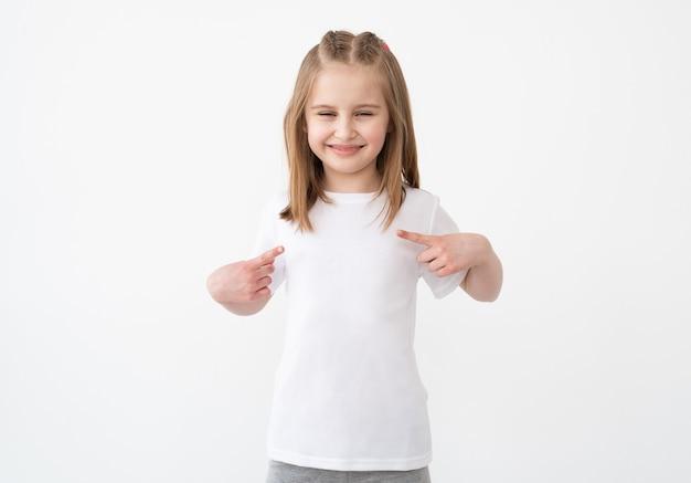 Schattig klein meisje wijzend op lege witte tshirt