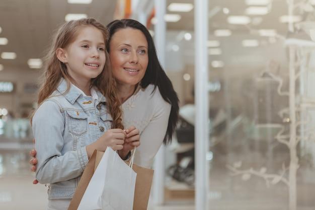 Schattig klein meisje winkelen in het winkelcentrum met haar moeder