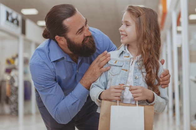 Schattig klein meisje winkelen in het winkelcentrum met haar vader