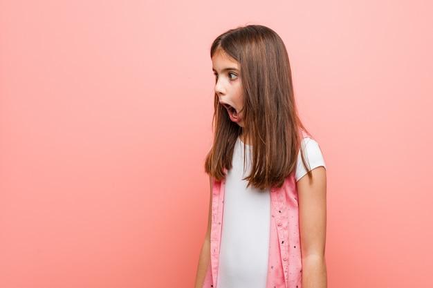 Schattig klein meisje wordt geschokt vanwege iets dat ze heeft gezien.