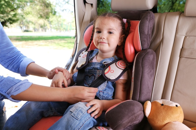 Schattig klein meisje zit in de auto