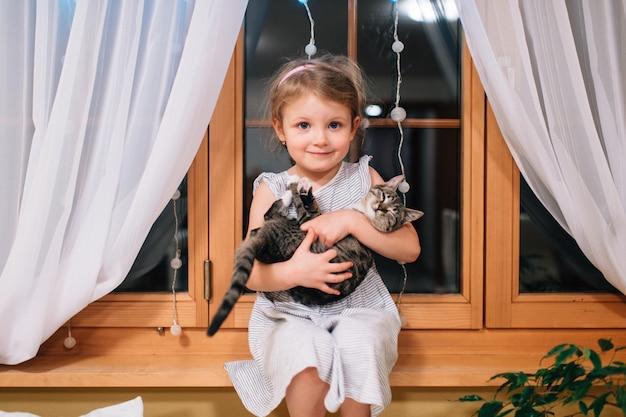 Schattig klein meisje zit in haar kamer op een vensterbank met kitten in haar handen
