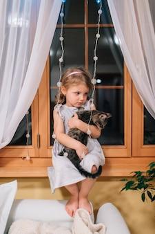 Schattig klein meisje zit in haar kamer op een vensterbank 's nachts.