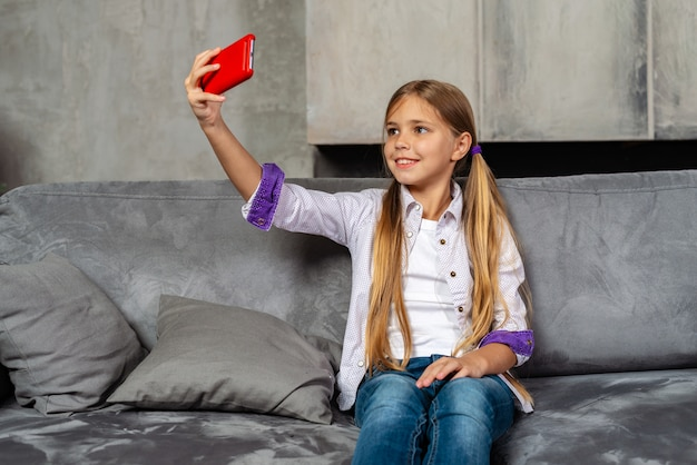 Schattig klein meisje zit op de bank en doet selfie op haar rode smartphone