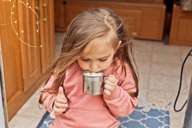 Schattig klein meisje zit op de trappen van een reisaanhanger en drinkt warme chocolademelk met marshmallows
