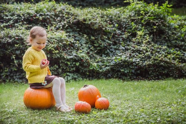 Schattig klein meisje zit op een pompoen