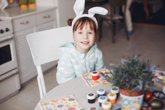 Schattig klein meisje, zittend in een keuken