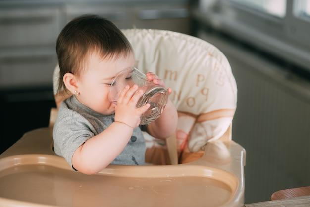 Schattig klein meisje, zittend in een kinderstoel in de keuken en drinkwater