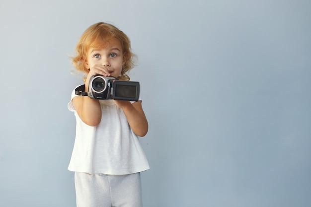 Schattig klein meisje, zittend in een studio op een blauwe achtergrond