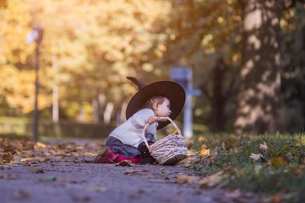 Schattig klein meisje zittend in het gras in het herfstbos op de achtergrond van de mand in