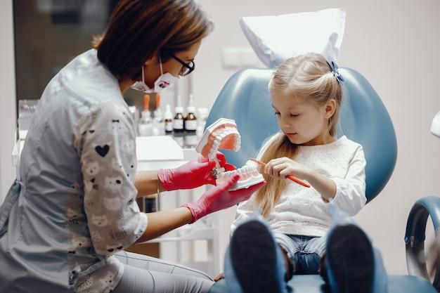 Schattig klein meisje, zittend in het kantoor van de tandarts