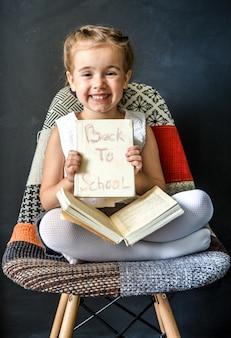 Schattig klein meisje, zittend op een mooie stoel met een boek in de hand, het concept van onderwijs en schoolleven