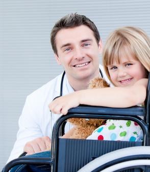 Schattig klein meisje, zittend op een rolstoel met haar arts