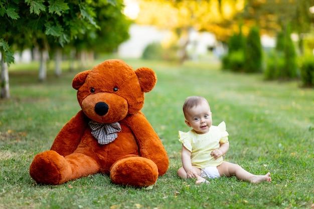 Schattig klein meisje zittend op groen gras met grote teddybeer in gele zomerjurk in de zomer.