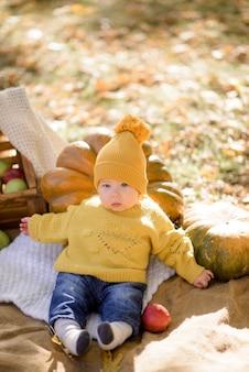 Schattig klein meisje zittend op pompoen en spelen in herfst bos