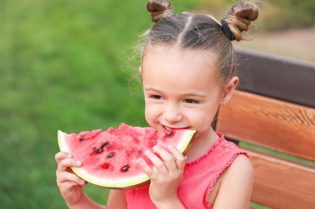 Schattig klein meisje zoete watermeloen eten in park