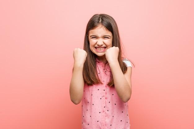Schattig klein meisje zorgeloos en opgewonden juichen. overwinning concept.