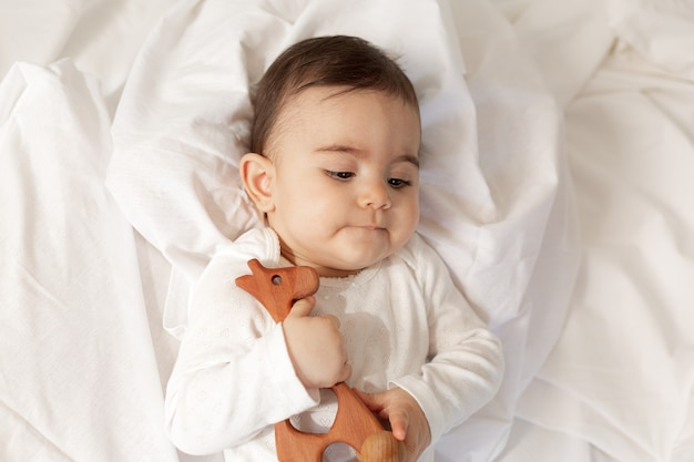 Schattig klein mestizo-meisje ligt in bed in een witte bodysuit met katoenen beddengoed, met een houten speelgoed in haar handen. hoge kwaliteit foto