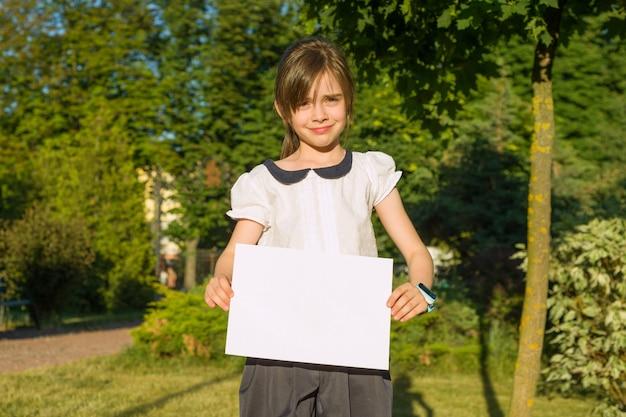 Schattig klein schoolmeisje met blanco vel papier
