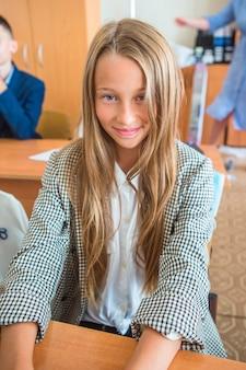 Schattig klein schoolmeisje met notities en potloden binnen
